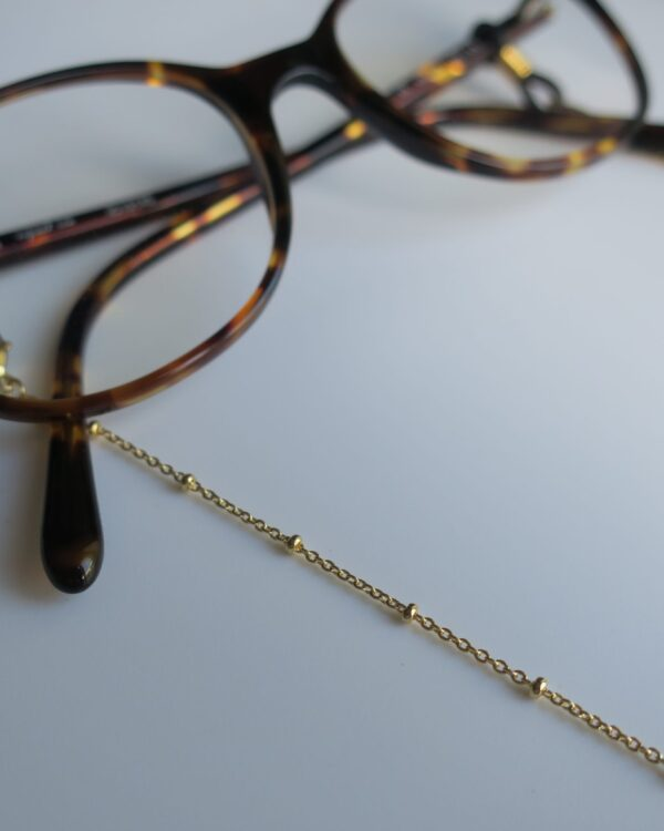 Chaînes de lunettes dorées.